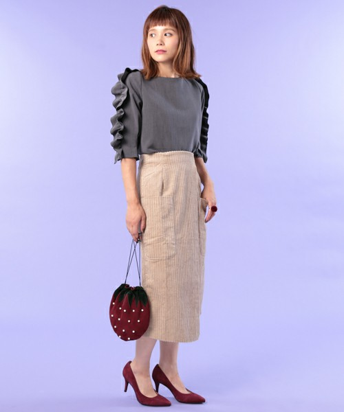 グレーのフリルトップスにベージュのスカートを合わせた女性