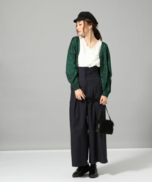白のブラウス・黒のワイドパンツにグリーンのカーディガンを着た女性