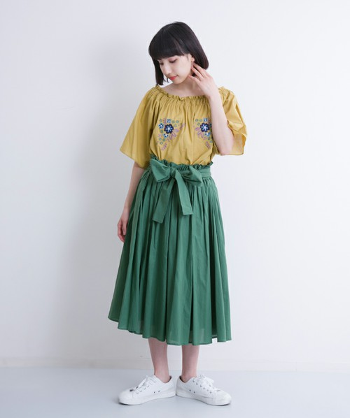 黄色の刺繍ブラウスと緑のスカートを合わせた女性