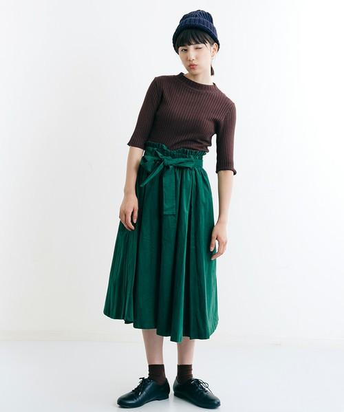 ブラウンのリブニットにグリーンのギャザースカートを履いた女性