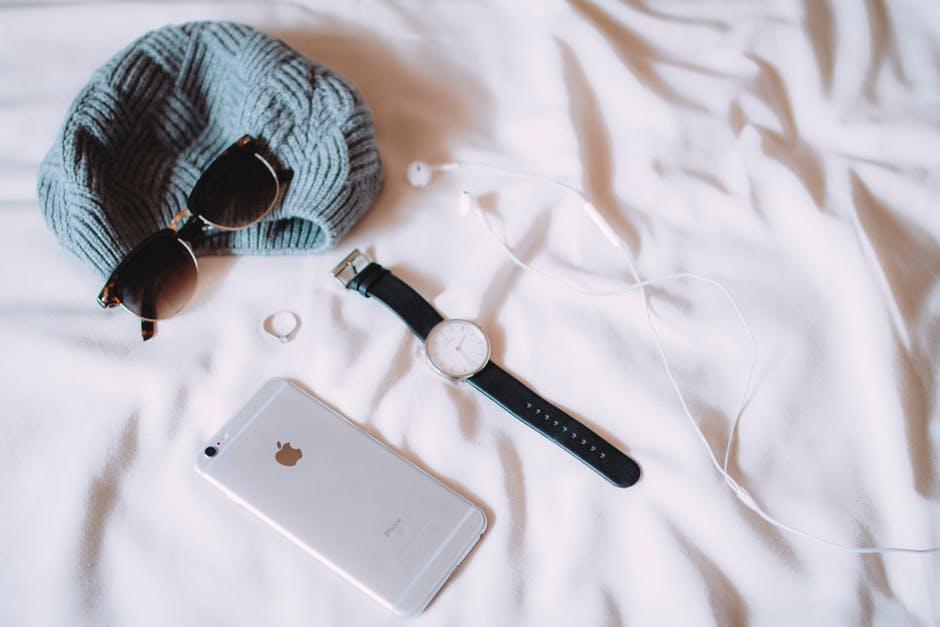 iPhoneとサングラスや腕時計などファッション小物がのっている白いベッド