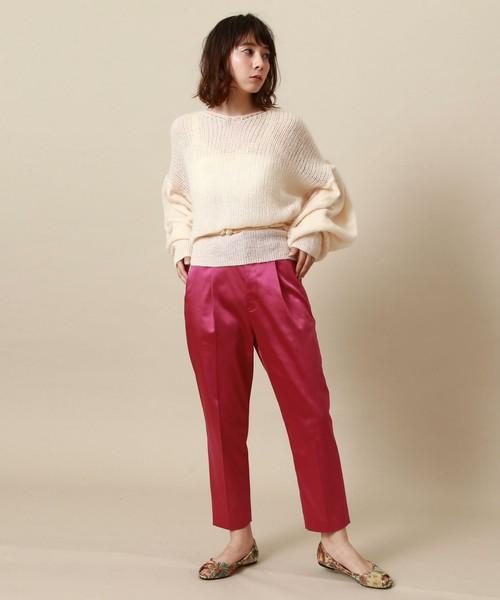 白いニットにピンクのサテンパンツを合わせた女性