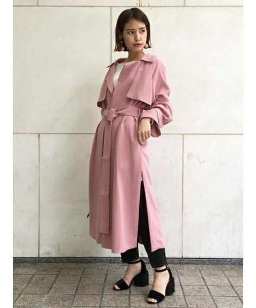くすみピンクのトレンチコートを羽織った女性