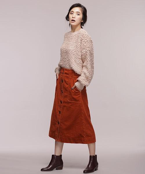 ピンクニットにテラコッタのスカートを合わせてブラウンのブーツを履いた女性
