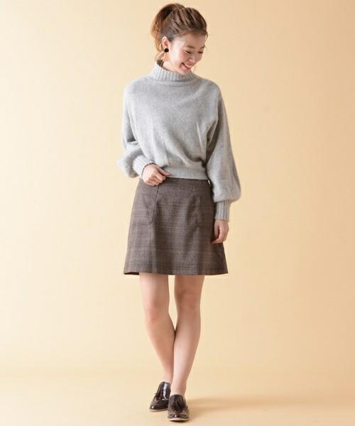 グレーのニットにグレンチェックのスカートを合わせてローファーを履いた女性
