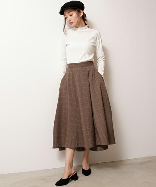 白いトップスにグレンチェックのスカートを合わせて黒いミュールを履いた女性