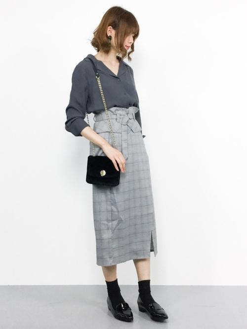 グレートップスにグレンチェックのスカートを合わせて黒いバッグを持った女性