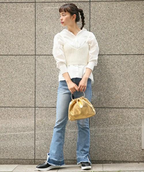 白のシャツにニットビスチェとゴールドのメタリックバッグを合わせたコーデ