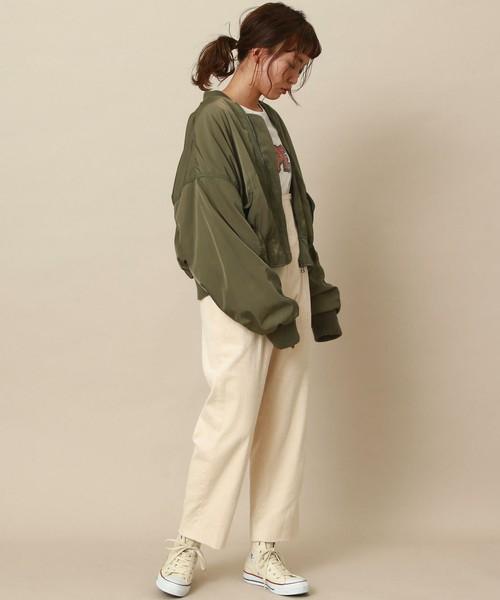 白トップスに白ワイドパンツを合わせてカーキのブルゾンを羽織った女性