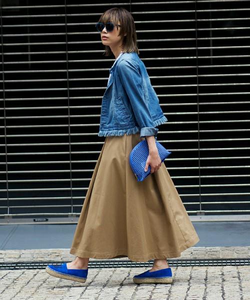 Gジャンにベージュのスカートを合わせる女性