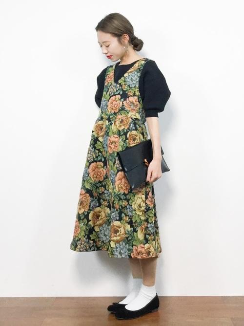 黒ブラウスに花柄のジャンバースカートを合わせてバレエシューズを履いた女性