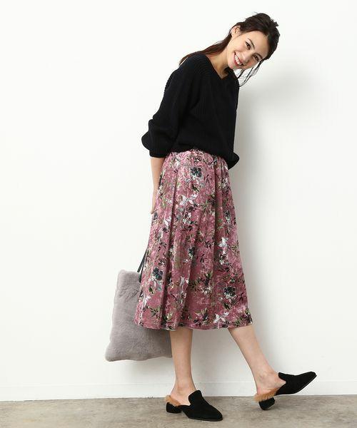 黒トップスにピンクのベロアの花柄スカートを合わせた女性