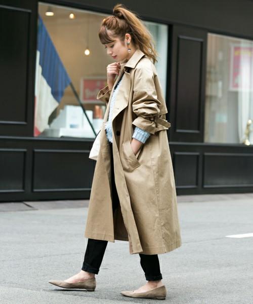 ビッグシルエットのトレンチコートを着た女性