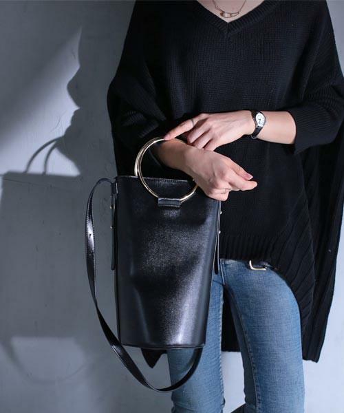 黒のフープ付きバケツバッグを持った女性