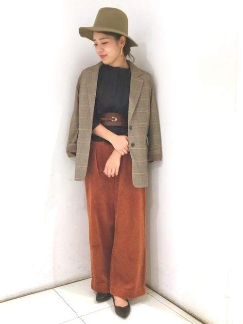 黒ブラウスにテラコッタのワイドパンツを合わせてグレンチェックのジャケットを羽織った女性