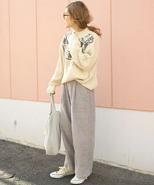 白ニットにグレーワイドパンツを合わせて白いスニーカーを履いた女性