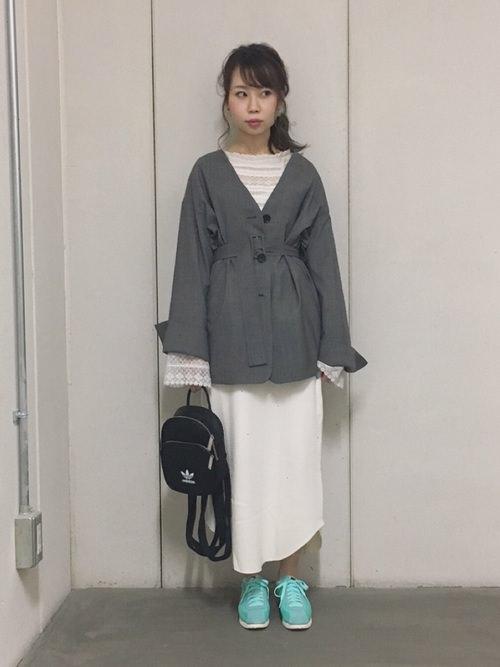 グレーのジャケットに白スカートとナイキスニーカーを履いた女性