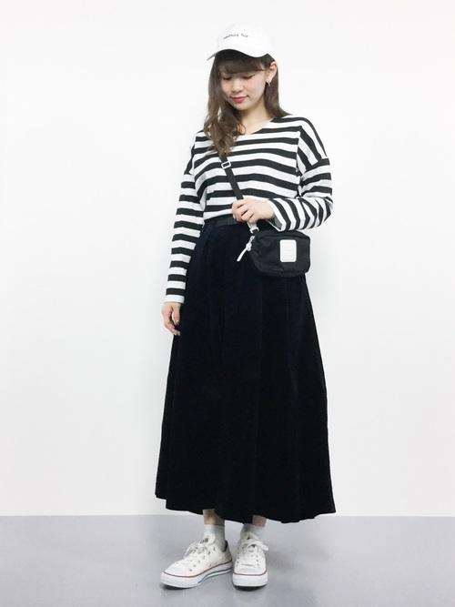 ボーダートップスに黒のボリュームスカートを履いた女性