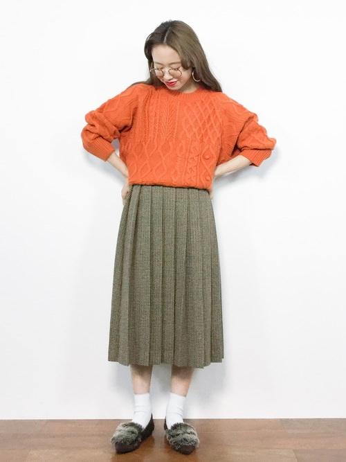 オレンジのニットに茶色のスカートを合わせた女性