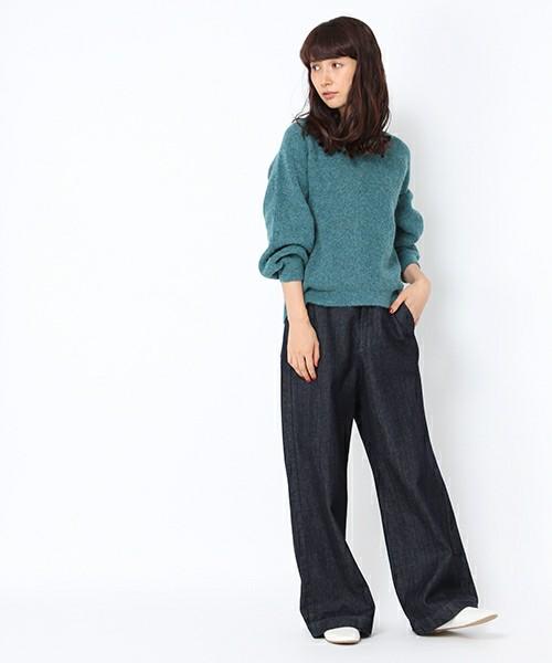 グリーンのニットにデニムワイドパンツを履いた女性