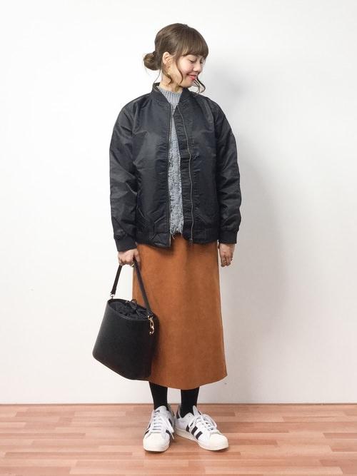 グレーのセーターに黒ブルゾンを羽織り、ブラウンのロングスカートを穿いた女性