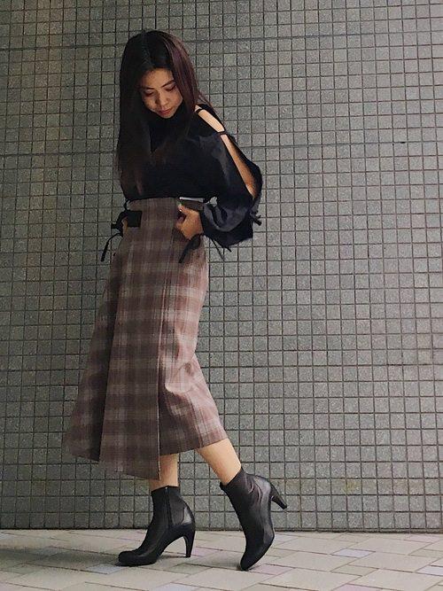 オープンショルダーの黒シャツにグレンチェックのラップスカートを合わせた女性