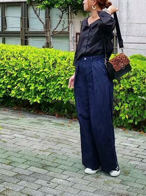 黒シャツにバギーデニムを合わせた女性