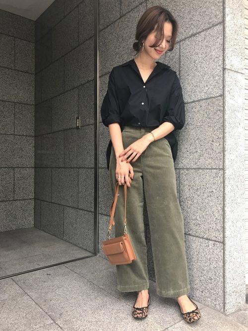 黒シャツにコーデュロイのワイドパンツを合わせた女性