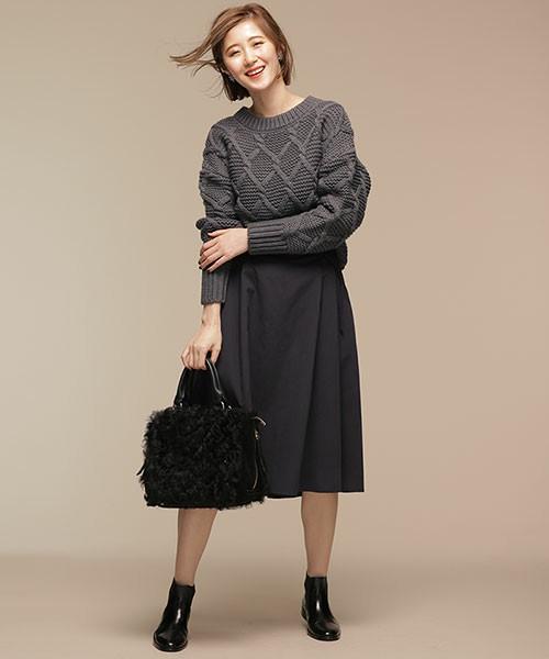 チャコールのケーブルニットに黒のフレアスカートを履いた女性