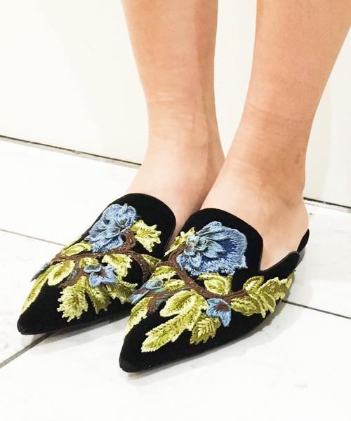黒に花柄刺繍されたバブーシュを履いた女性