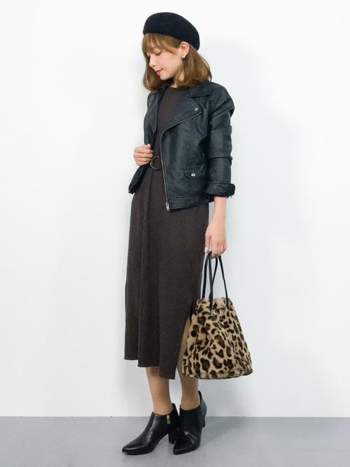 ブラウンのリブニットワンピースに黒のライダースジャケットを着た女性
