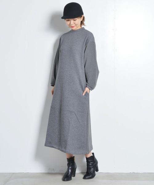 グレーのハイネックワンピースを着た女性
