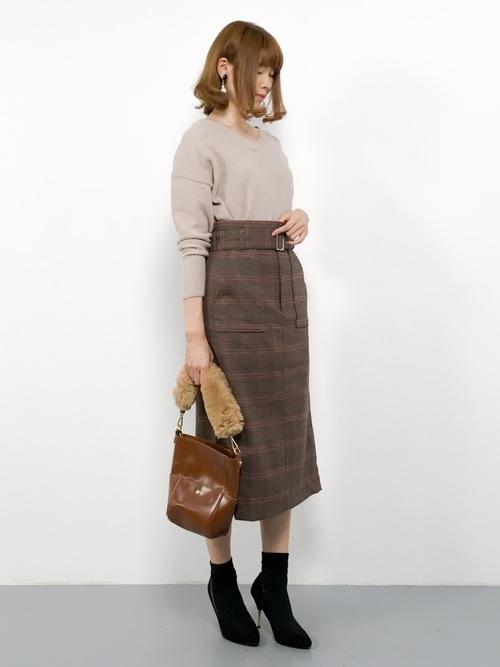 ベージュのVネックニットにグレンチェックのラップスカート、ファーハンドルバッグを持った女性