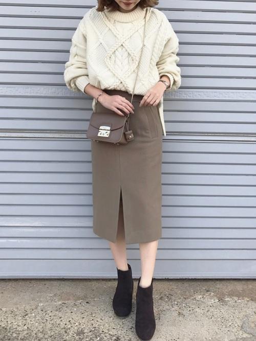 白いニットにベージュのスカートを合わせて黒いショートブーツを合わせた女性