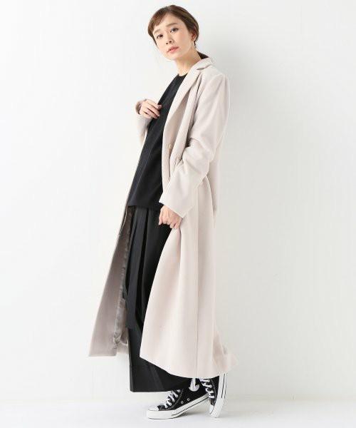 黒のトップス、スカートに白のロングチェスターコートを着た女性