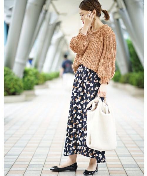 キャメルのモールニットに花柄スカートを履いた女性