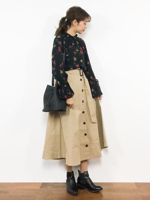 花柄ブラウスにベージュのトレンチ風スカートを履いた女性