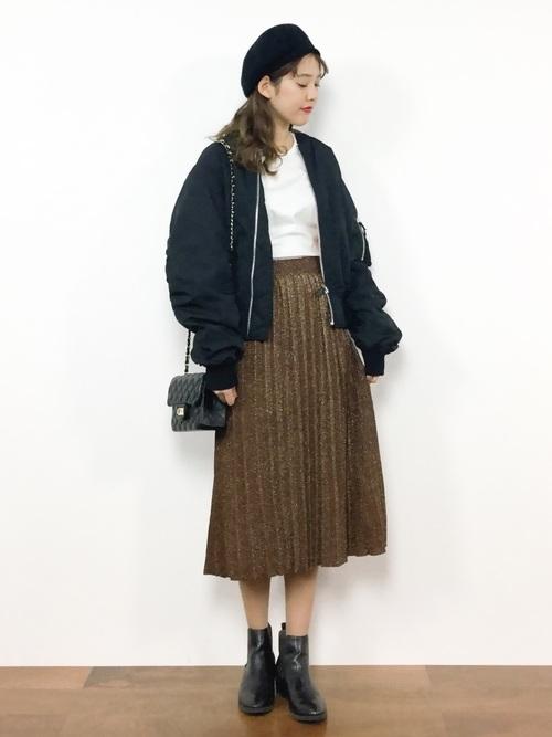 白のトップス、ブラウンのラメプリーツスカートに黒のMA-1を着た女性