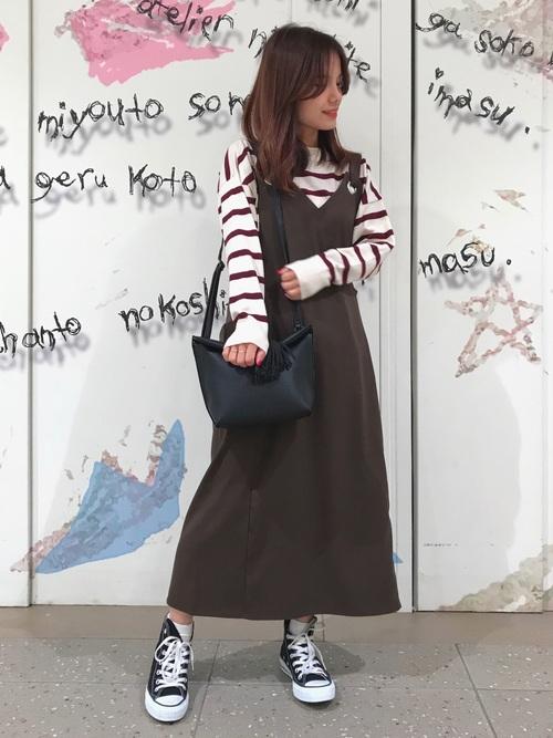 ボーダーニットにジャンパースカートを合わせた女性