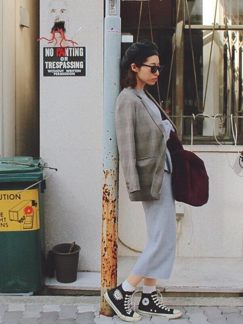 チェックのジャケットにニットのタイトスカートを合わせてスニーカーを履いた女性