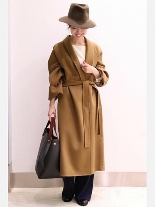 白のトップス、ネイビーのリブニットパンツにキャメルのガウンコートを着た女性