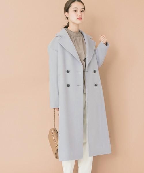 ベージュのブラウスと白いパンツを合わせて、水色のPコートを羽織った女性