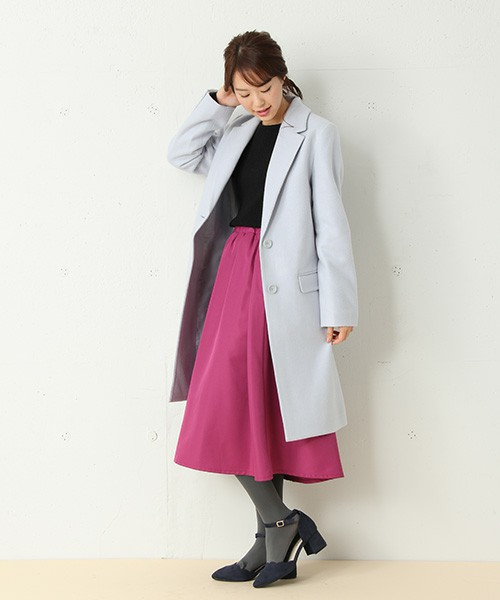 黒のトップスにピンクのスカートを合わせて、水色のチェスターコートを羽織った女性