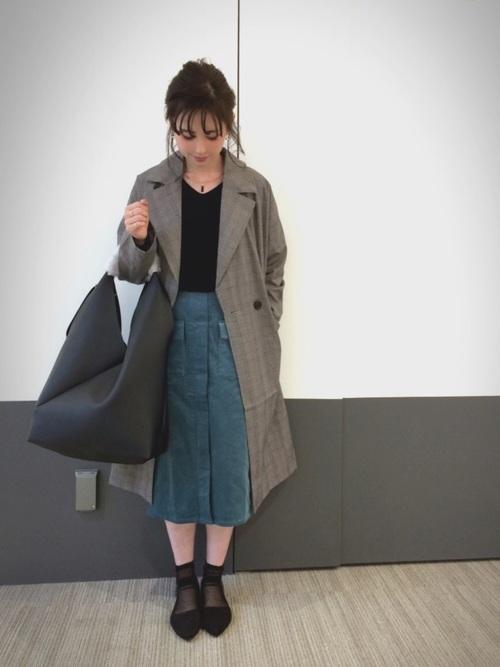 黒のトップス、グリーンのスカートのグレンチェックのチェスターコートを着た女性