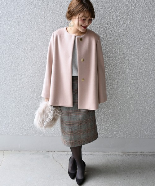 ピンクのコートにチェックのスカートを合わせてファーバッグを持った女性