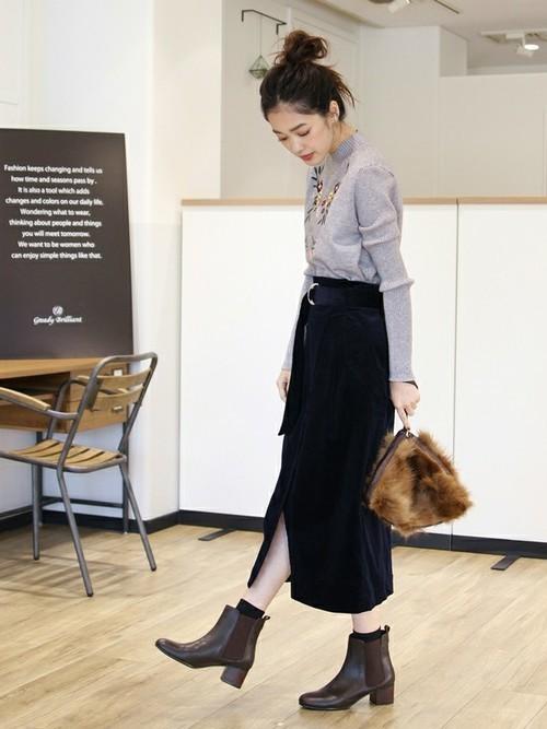 グレーのニットにスリットスカートを合わせてショートブーツを履いた女性