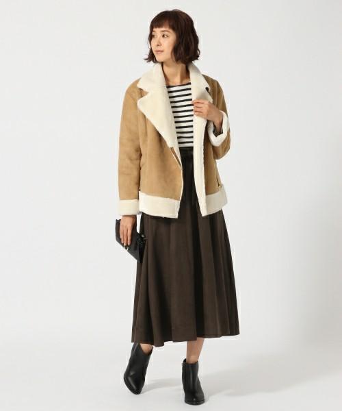 ボーダーのインナーにダークブラウンのスエードスカートを合わせてムートンコートを羽織った女性