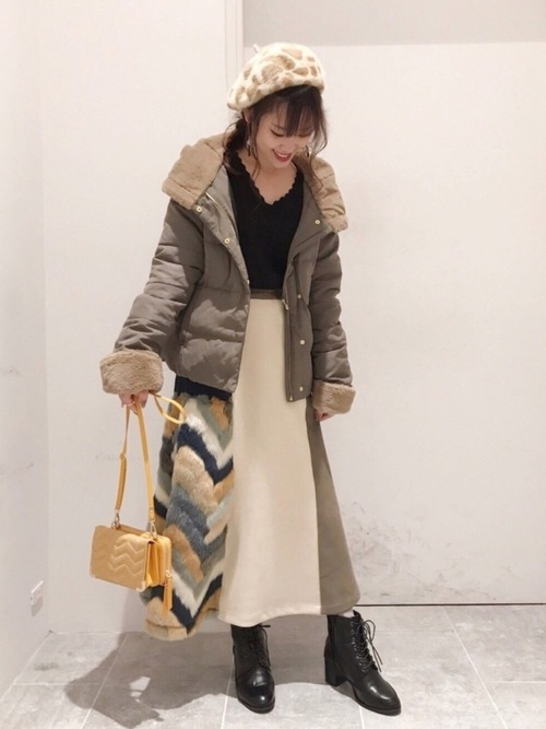 黒のトップスにファー×スエードスカートを合わせてダウンコートを羽織った女性