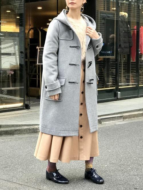 ベージュのニット、スカートにグレーのダッフルコートを着た女性