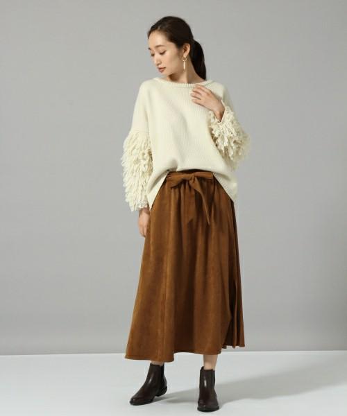 白ニットにキャメルのスエードスカートを合わせた女性